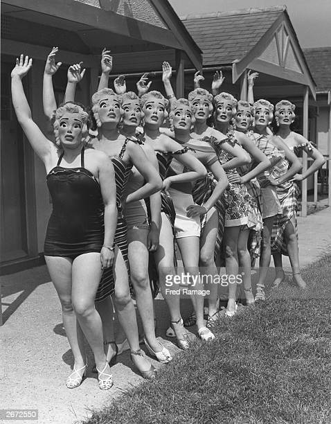 Women workers at Butlin's holiday camp wearing Marilyn Monroe face masks as they parade in their swimsuits