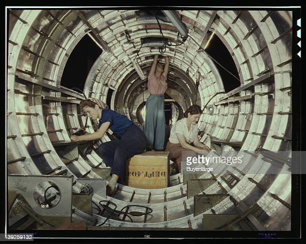 Women workers install fixtures and assemblies to a tail fuselage section of a B17 Flying Fortress bomber at the Douglas Aircraft Company plant Long...