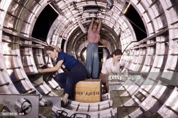 Women workers install fixtures and assemblies to a tail fuselage section of a B17 bomber at the Douglas Aircraft Company plant Long Beach Calif...