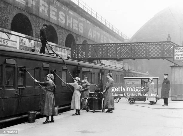 Women workers use a vacuum to clean a railway carriage on the South Eastern Chatham Railway