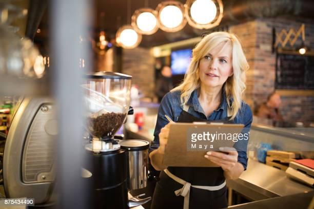 mujeres que trabajan en la cafetería - lista de chequeo fotografías e imágenes de stock