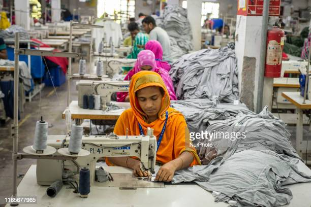 Women working equals to their male coworkers in terms of shifts and wages under proper working conditions in a Ready Made Garment factory at...