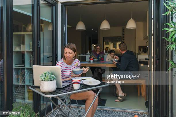 women working from home. bowl of pasta in hand. her family eat in the background - using laptop stock pictures, royalty-free photos & images