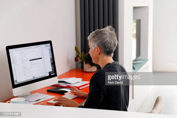 a women working from home looking at her computer screen. - leanincollection stock pictures, royalty-free photos & images