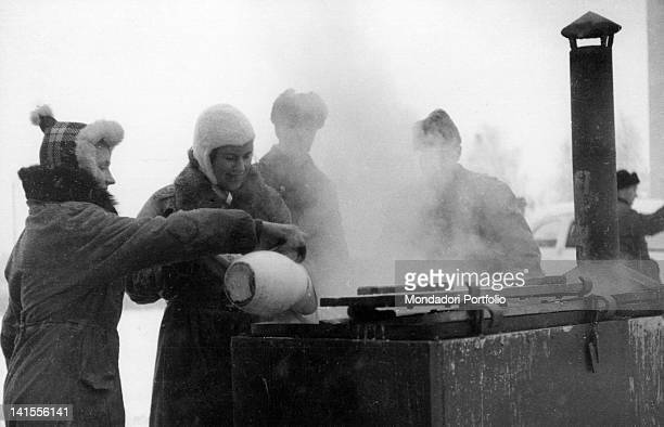 Women working in a military field kitchen to feed the foreign volunteers who have arrived to support the Finnish army Finland January 1940
