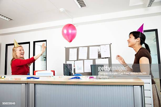 women working in an office wearing party hats