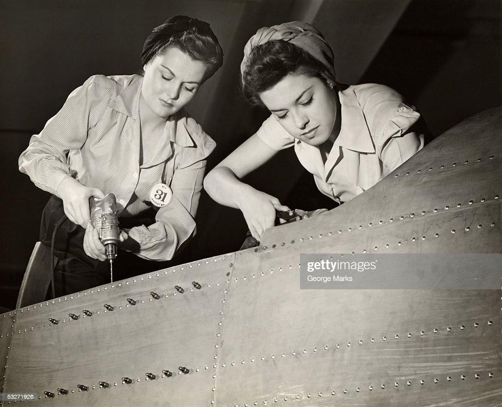 Women working on WW II aircraft assembly : Stock Photo