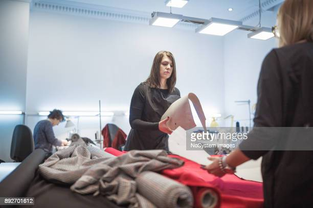 Women Working Together. Fashion designers working together, looking at fabric samples