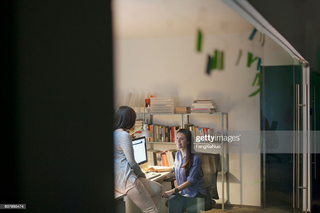Women working together in design studio at night : Stock Photo