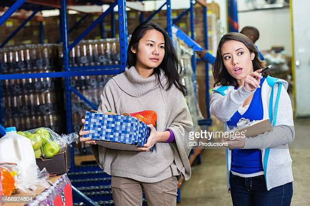 Women working together in food bank distribution warehouse