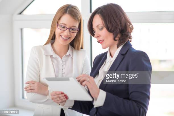 Women working together in office on digital tablet