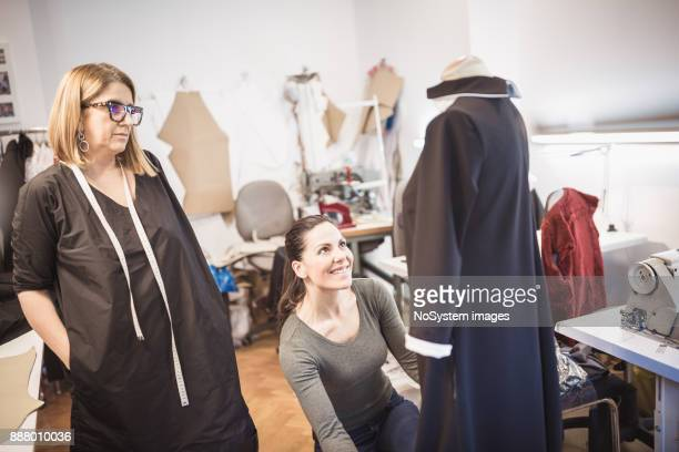 Women Working Together. Two famale tailors working together  on fashion model's dress in fashion design studio