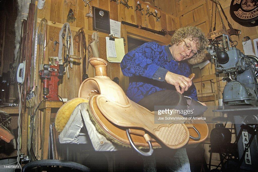 Women works on saddle at Three Forks Custom Saddlery, MT