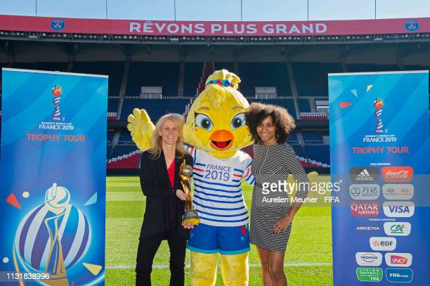 Women World Cup Legends Kristine Lilly and Laura Georges and FIFA Women's World Cup mascot Ettie pose next to the World Cup trophy during the FIFA...