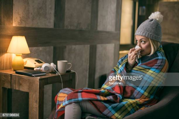 women wrapped at blanket having flu at home - cold virus stock pictures, royalty-free photos & images