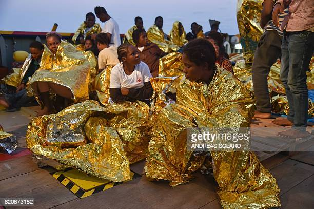 Women wrapped in a survival foil blanket rest aboard the Topaz Responder ship run by Maltese NGO Moas and the Italian Red Cross after a rescue...