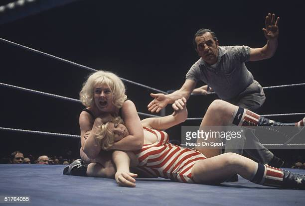 Women wrestle while a referee makes the countdown circa 1970's