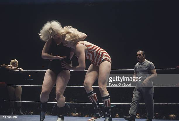 Women wrestle while a referee stands watching circa 1970's