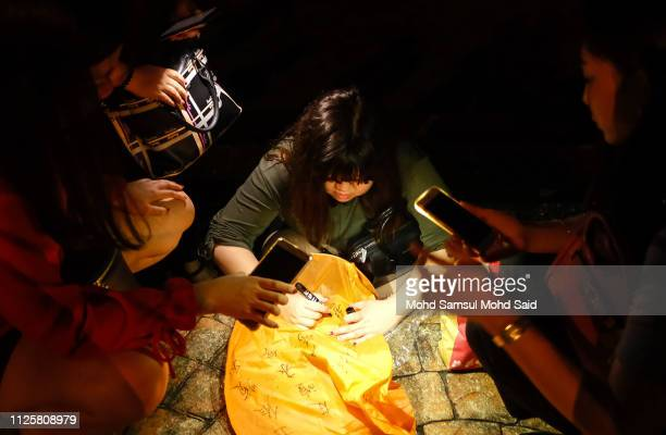 A women write a prayer message on flying lantern's near the North port during Chap Goh Meh celebrations to mark the end of Chinese New Year Of The...