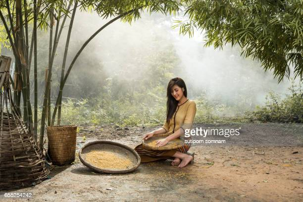 Women young farmers harvest or separate rice