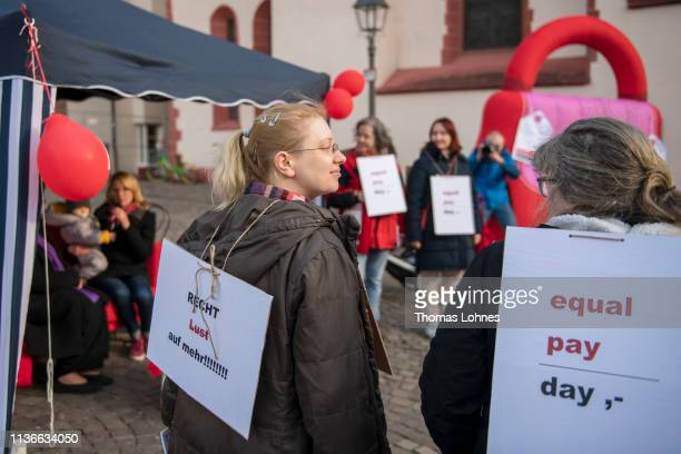 Womenprotest in front of a the effigy of a giant purse to demand equal pay for women on Equal Pay Day on March 18, 2019 in Frankfurt, Germany. Women...