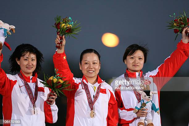 Women's 10m Air Pistol Chinese team shooters Tao Luna Guo Wenjun and Ying Chen celebrate their gold win at the 15th Asian Games at the Lusail...