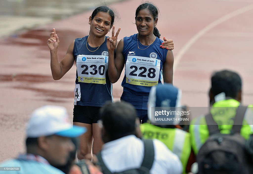 Women's 200 meters respective silver and bronze medal winners from India Asha Roy (R) and Dutee Chand flash victory signs after their race on the fifth and the final day of the Asian Athletics Championship 2013 at the Chatrapati Shivaji Stadium in Pune on July 7, 2013. AFP PHOTO/Manjunath KIRAN