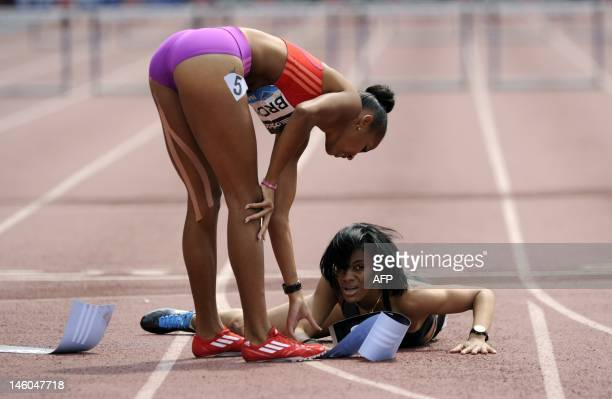 Women's 400meter hurdles winner T'erea Brown of the US helps Kaliese Spencer of Jamaica at the finish line during the 2012 Adidas Grand Prix on June...