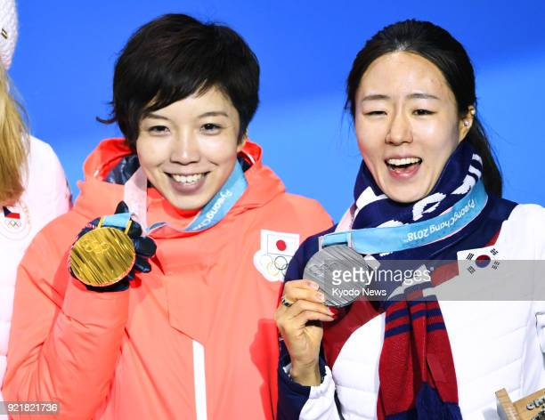 Women's 500-meter speed skating gold medalist Nao Kodaira of Japan and silver medalist Lee Sang Hwa of South Korea attend the medal ceremony at the...
