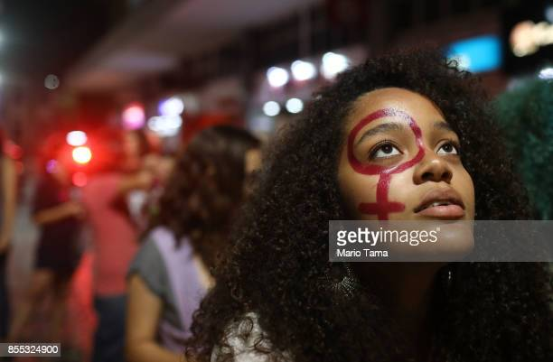 Women's activists march for pro-choice rights past street art displayed on a wall on September 28, 2017 in Rio de Janeiro, Brazil. Brazilian law...