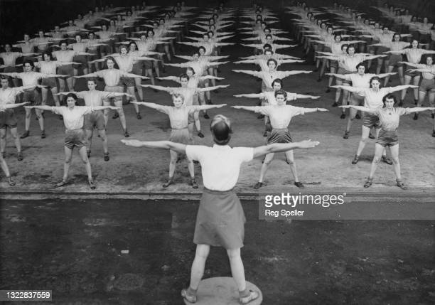 Women's Auxiliary Air Force physical education instructor gives aerobic exercise instructions to a group of ACW Aircraftwomen on 24th June 1943 at...