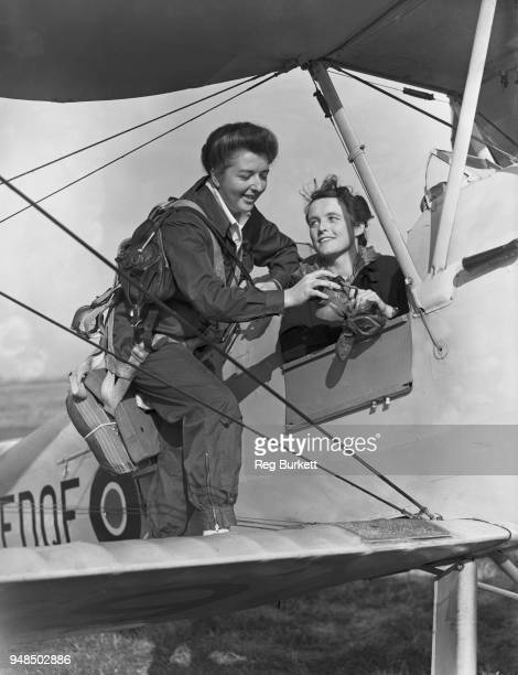 Women's Auxiliary Air Force pilots Margot Gore and Joan Nayler preparing for a flight in a Tiger Moth II biplane after being the first two recruits...