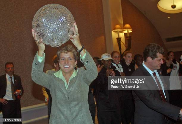 Women's Basketball Coaches Association president Beth Bass hold up the Sears Trophy given to University of Connecticut women's basketball team after...