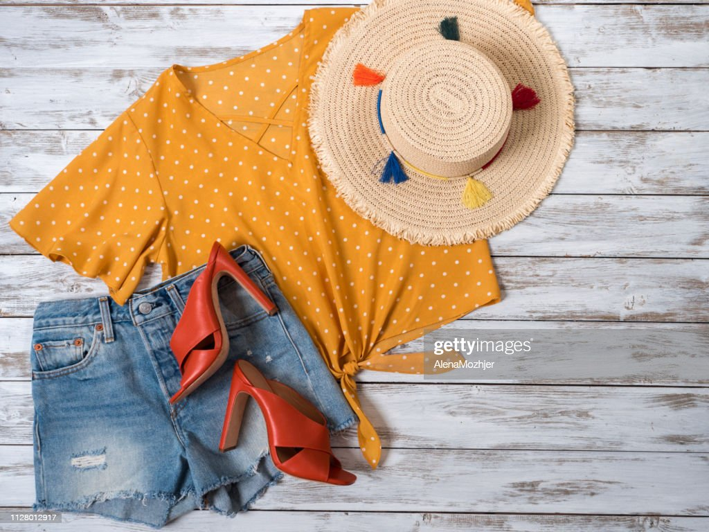Womens clothing, accessories, footwear (leather mule heels shoes, denim shorts, yellow blouse in polka dot, straw hat). Fashion outfit, spring summer collection. Shopping concept. Flat lay, view from above : Stock Photo