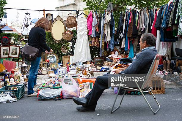 Women's clothing hangs on a rail as a customer left browses other items for sale at Feira da Ladra flea market in Lisbon Portugal on Saturday Oct 12...