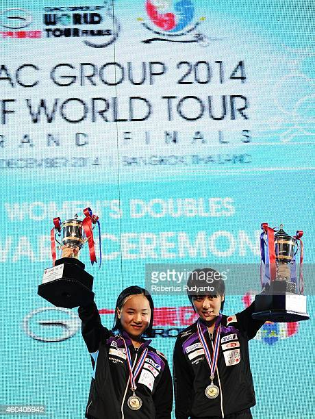 Women's double winner Miu Hirano and Mima Ito of Japan pose with the trophy during the awarding ceremony of the 2014 ITTF World Tour Grand Finals at...