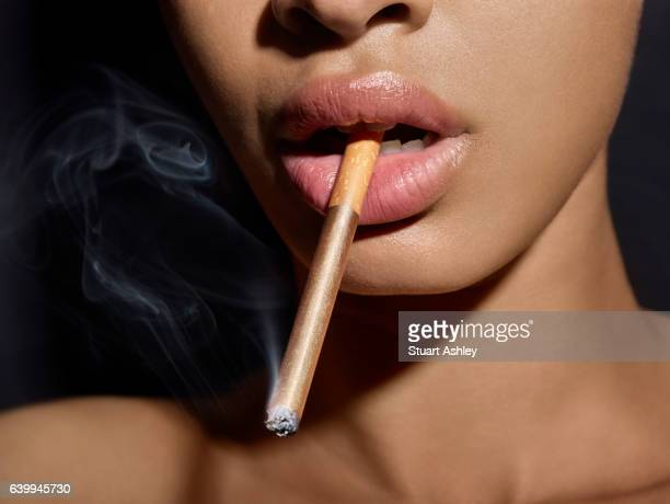 womens face with gold cigarette in mouth, between lips
