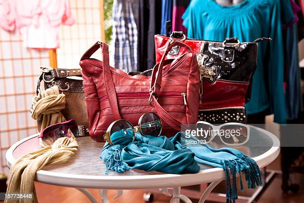 Women's fashion accessories in retail store window display. Purses, clothes.