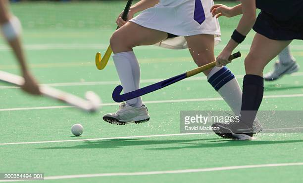 Women's field hockey players in action, low section