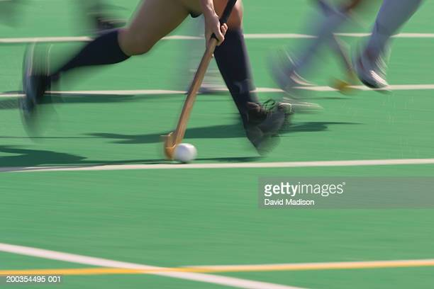 Women's field hockey players in action, low section (blurred motion)