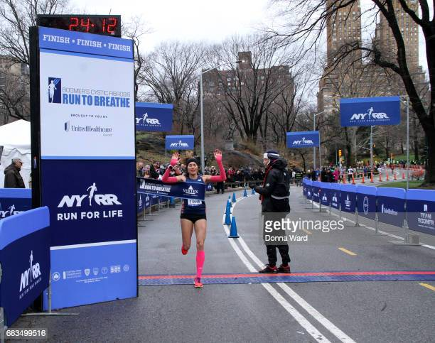 Womens finisher the tape crosses the finish line during Boomer's Cystic Fibrosis 'Run To Breathe' Charity Event at Central Park Bandshell on April 1...
