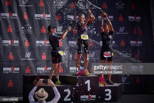 Women's first place athlete Beate Goertz second place Sandra Fantini and third place Nele Siegmeier spray champagne over themselves at the top three...