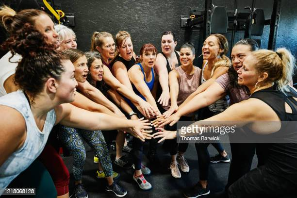 womens fitness class with hands together after workout in gym - leanincollection ストックフォトと画像