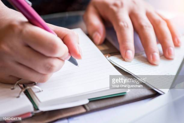 Women's hand calculates daily income