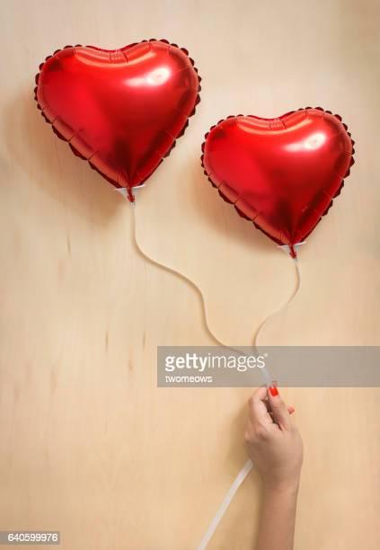 Women's hand holding heart shape balloons.