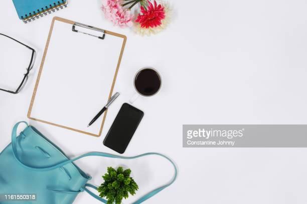 women's handbag and clipboard on white desk - feminidade - fotografias e filmes do acervo