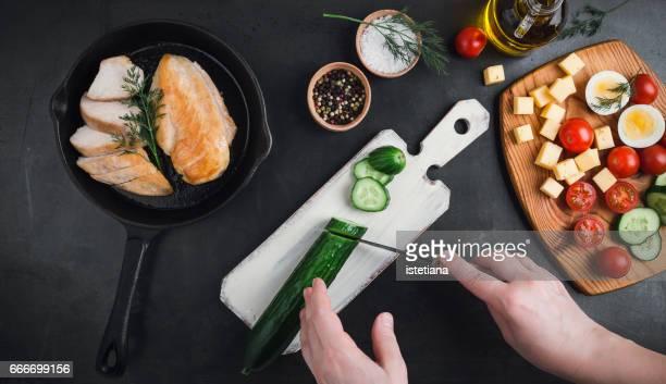 women's hands cutting cucumber, preparation salad,  top view - cortando preparando comida - fotografias e filmes do acervo