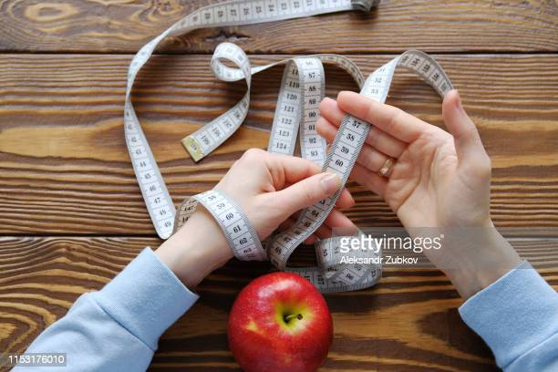 women's hands holding measuring tape on a wooden background. the concept of diet, healthy lifestyle and proper nutrition. copy space. weight loss, weight loss, vegetarian diet. minimalism in food - fasting activity stock pictures, royalty-free photos & images