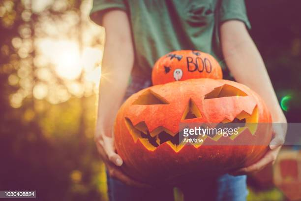 women's hands holding pumpkins - happy halloween stock photos and pictures