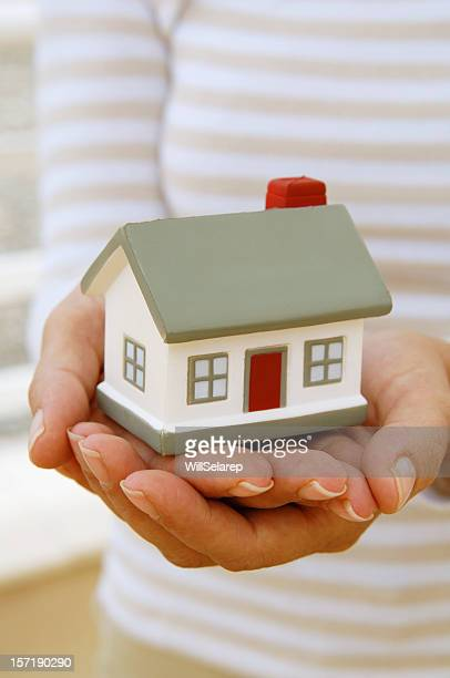 Women's hands with a little house